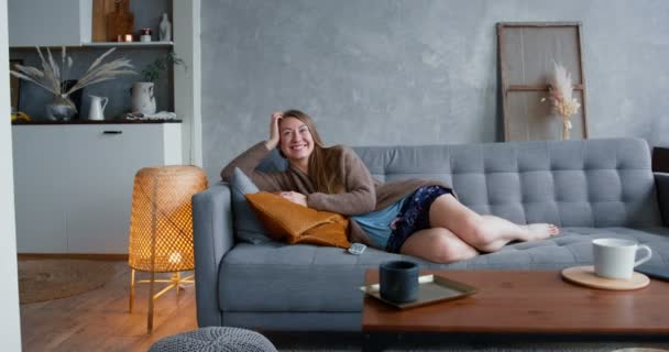 TV serials addiction. Young happy beautiful Caucasian blonde woman smiles watching comedy movie at home on cozy sofa.