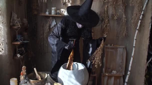 Čarodějnice halloween připravuje lektvar v kotli