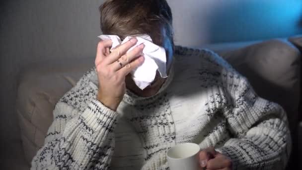 Nemocný muž vysmrkal v tkáni, mladý nemocný muž v posteli drží tkáň čištění domýšlivý nos s teplotou pocit bad infikovaných virem grippe zimní chřipky a chřipky koncepce zdravotní péče