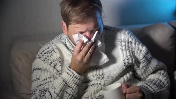 Kranker Mann bläst seine Nase in das Gewebe, junge kranke Mann im Bett halten Gewebe Reinigung snotty Nase mit Temperatur Gefühl schlecht infiziert durch Winter-Grippe-Virus in Grippe und Grippe Gesundheitskonzept