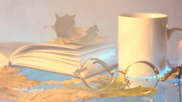 bílý čaj cup, brýle, knihy a podzimní listí na šedém pozadí