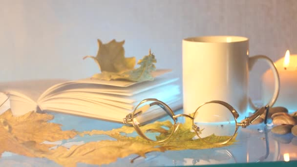 white tea cup, glasses, book and autumn leaves on gray background