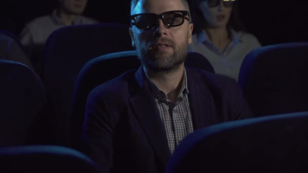 terrified man watches a horror film at the cinema