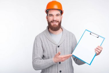 A constructor smiling and pointing at a paper holder near white background.