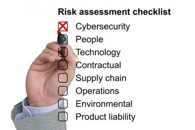 Hand crosses off first item of a risk assessment checklist