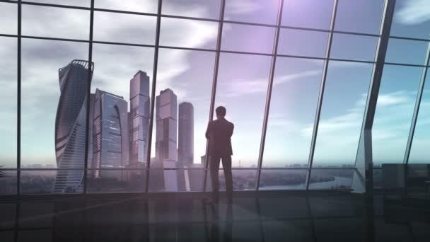 Byznysmen v kanceláři s výhledem na obchodní centrum.
