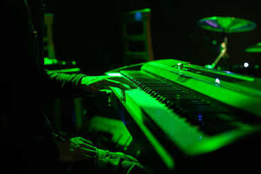 Man playing on synthesizer keyboard on stage during concert