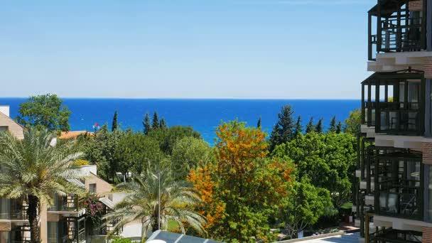 krajina v windy letní den, výhled z okna, zelené a oranžové stromy, palmy, průčelí budovy