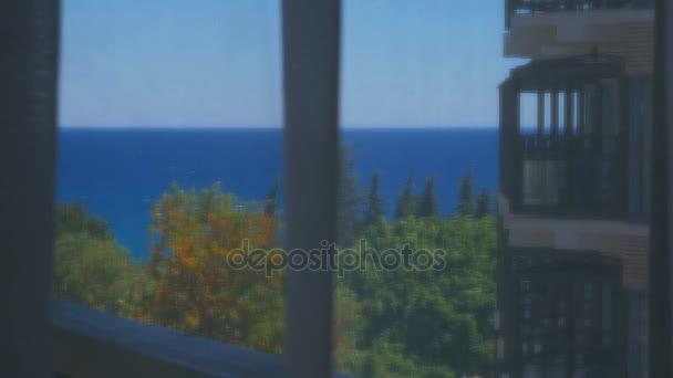 Seascape prostřednictvím bílé průhledné opony, pak závěs je tlačen zpět, po nasátí závěs