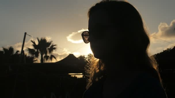 silhouette of young woman taken against sun, touching sunglasses, turning head, dramatic shot