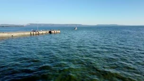 dron létá nízko nad řekou, vedle mola s lidmi a následující malé lodi slunečný den
