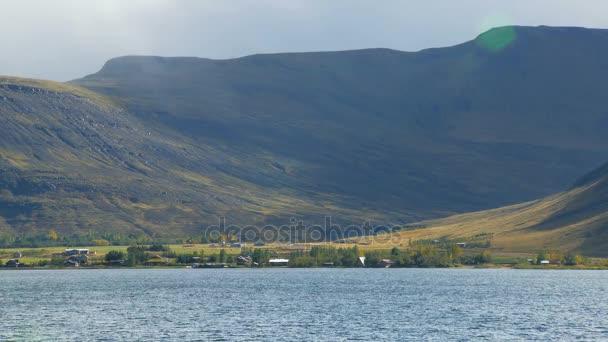 plochý sklon obrovské hory a malé chaty poblíž jezera na Islandu, krajina vesnice