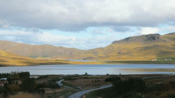 klidné jezero mezi kopci na Islandu, malé domy jsou na břehu, nízké bílé mraky
