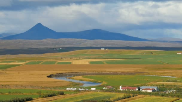 rural suburban landscape in Iceland in sunny autumn day, calm river, mountains, agricultural fields