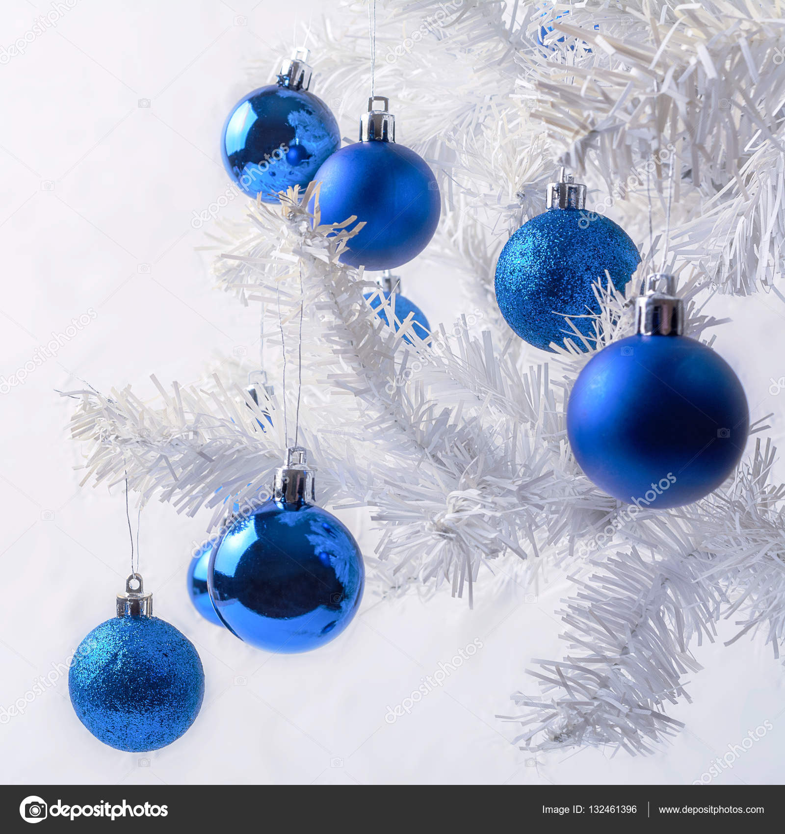 white christmas tree branch with royal blue ornaments christmas greeting background photo by tasipas