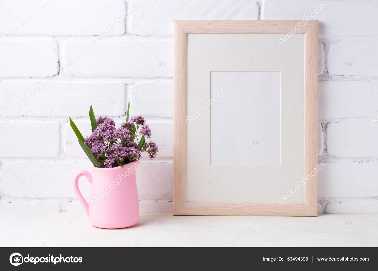Maqueta de marco de madera con flores de color púrpura en la jarra ...