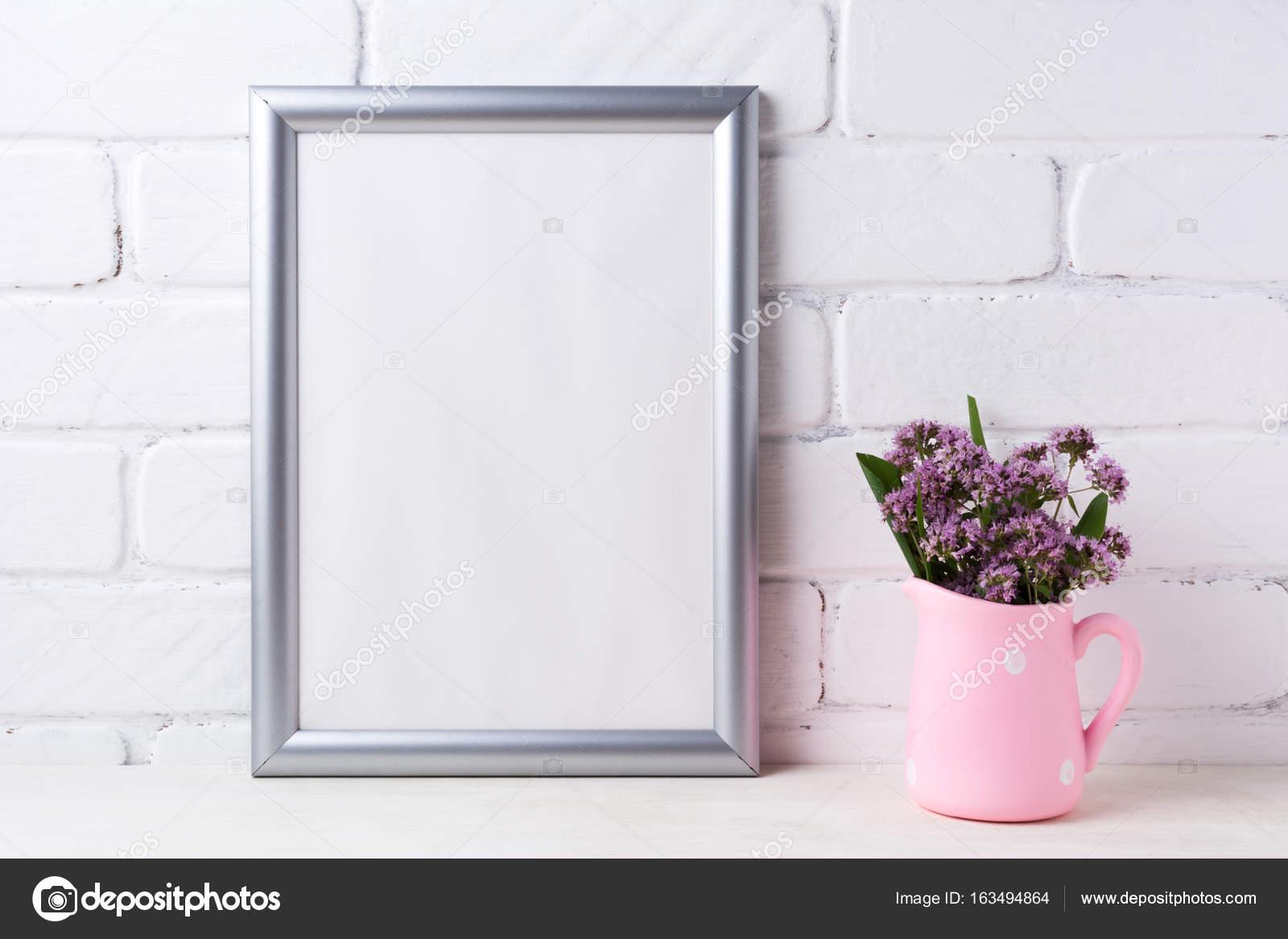 Maqueta de marco de plata con flores de color púrpura en la jarra ...