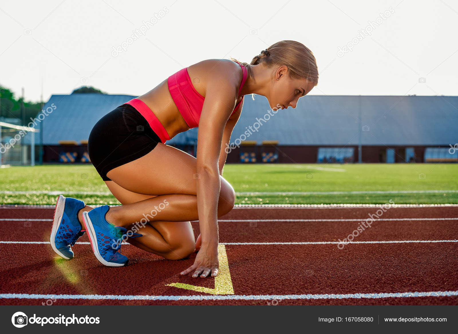 Young Woman Athlete At Starting Position Ready To Start A Race On Racetrack Stock