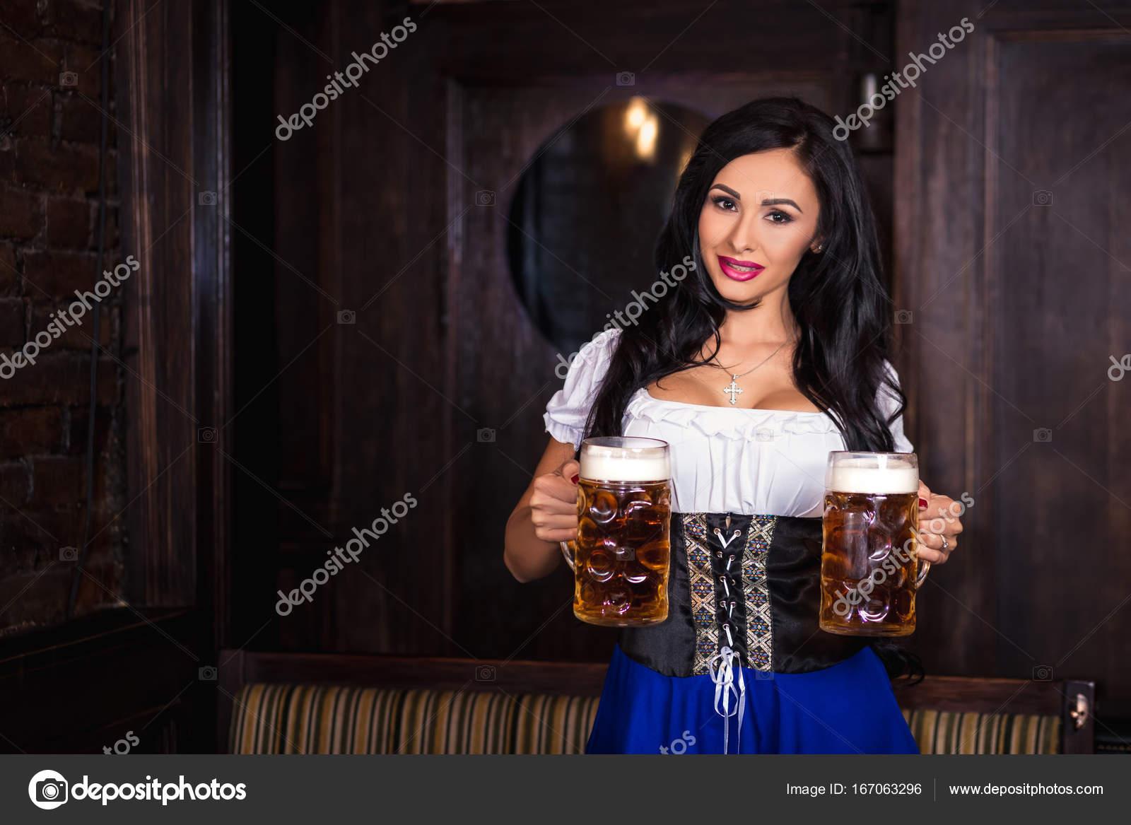 9c8f966ce0 Oktoberfest nő visel egy hagyományos bajor ruha Dirndli jelentenek egy  korsó sör a bárban — Stock