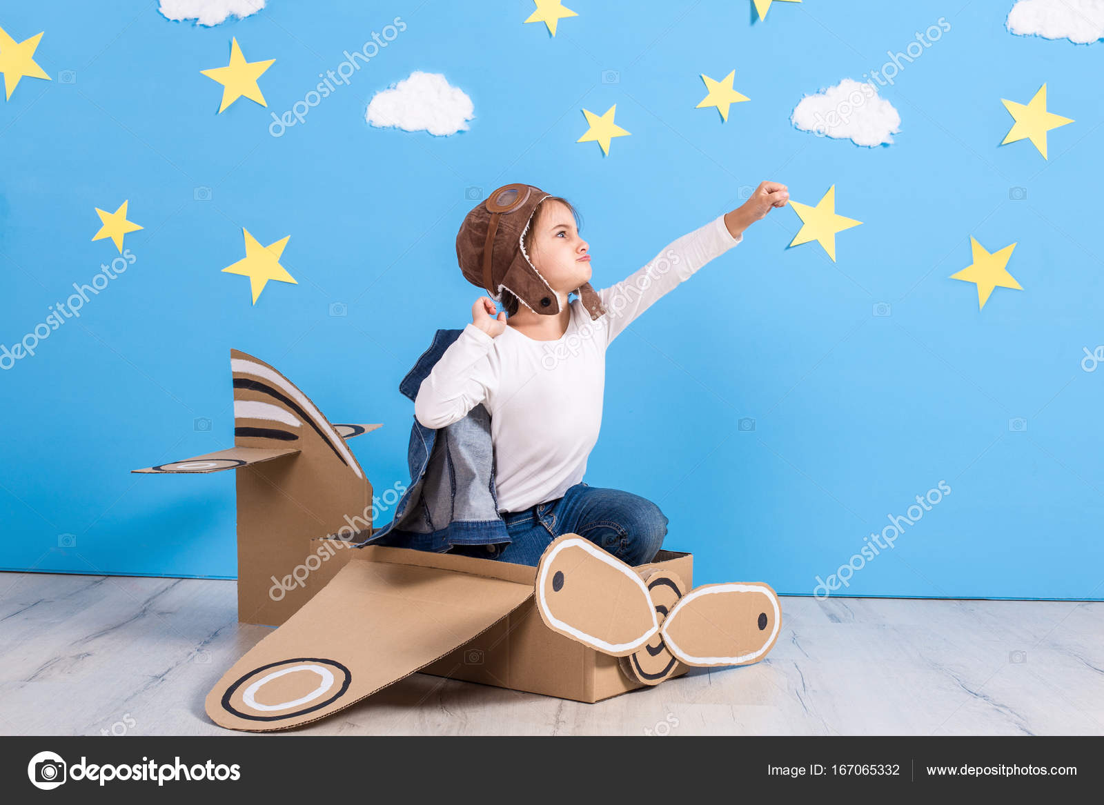 Little Child Girl In A Pilots Costume Is Playing And Dreaming Of Flying Over The Clouds