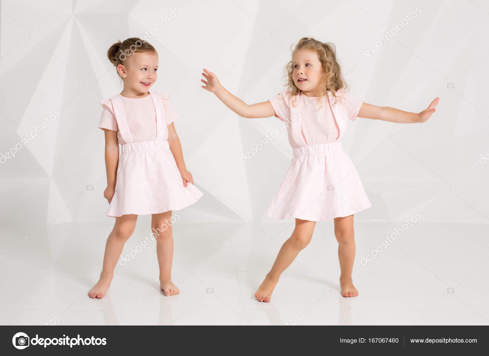 6c6832fad95b Δύο λίγο αστεία και γελώντας κορίτσι σε απαλά ροζ φορέματα, θέτοντας σε  λευκό studio. Όμορφη μικρή μόδα μοντέλα σε φόντο λευκό στούντιο — Εικόνα  από ...