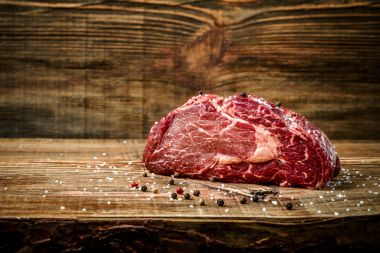 Dry aged Ribeye Steak with seasoning on wooden background.