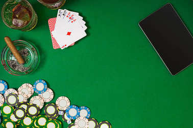 Set to playing poker with cards and chips on green table, top view
