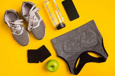 Fitness accessories on a yellow background. Sneakers, bottle of water, smart and sport top.