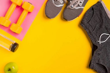Fitness accessories on a yellow background. Sneakers, bottle of water, apple and dumbbells.