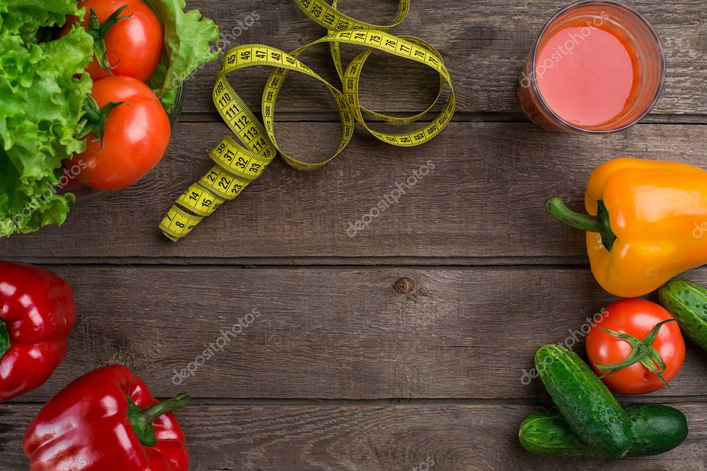 Glass of tomato juice with vegetables and measuring tape on table close-up