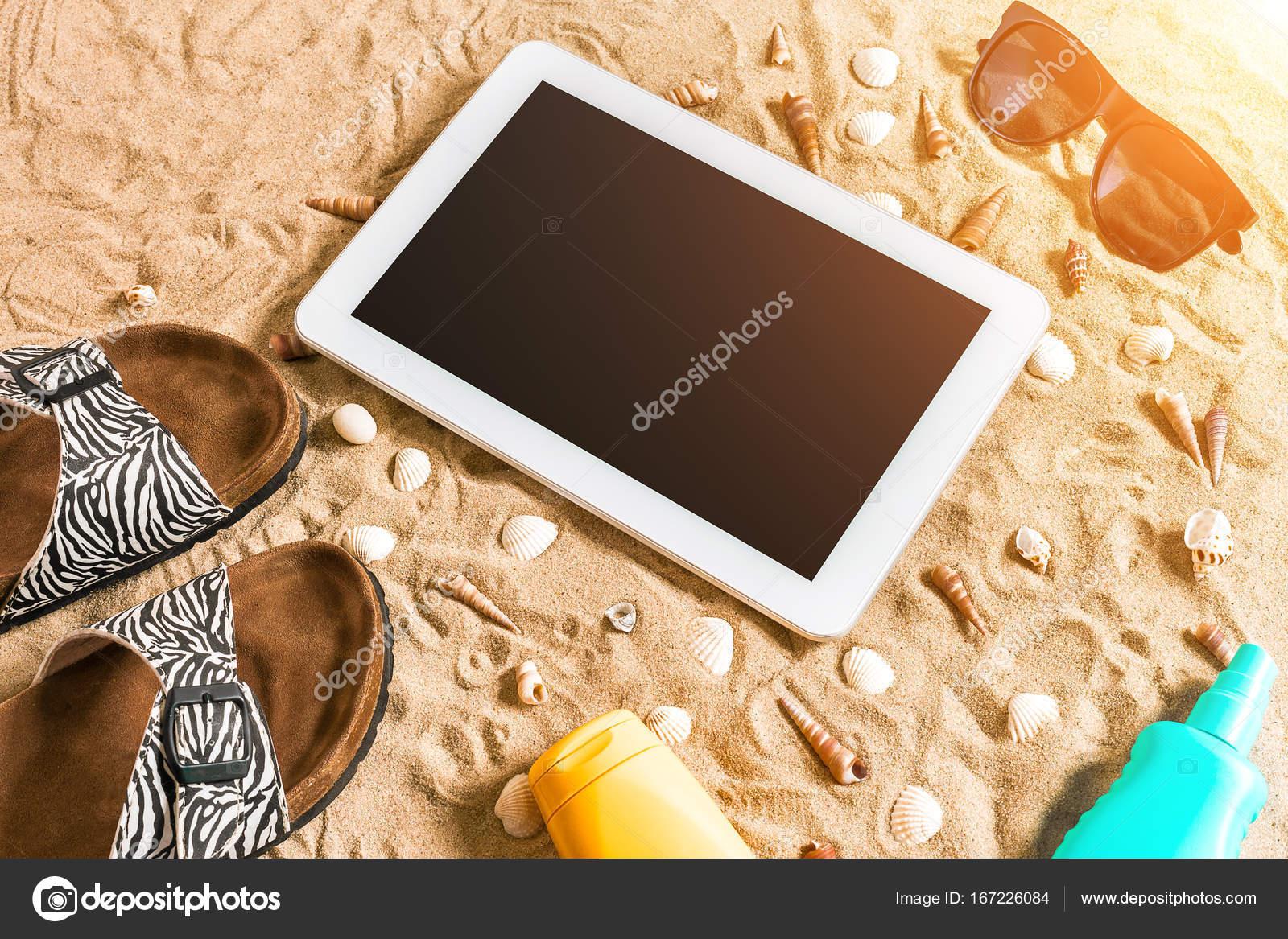 Chanclas de verano, tablet, gafas de sol y la concha en la arena ...