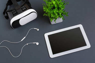 Virtual reality glasses and tablet with headphones on a gray background. Top view