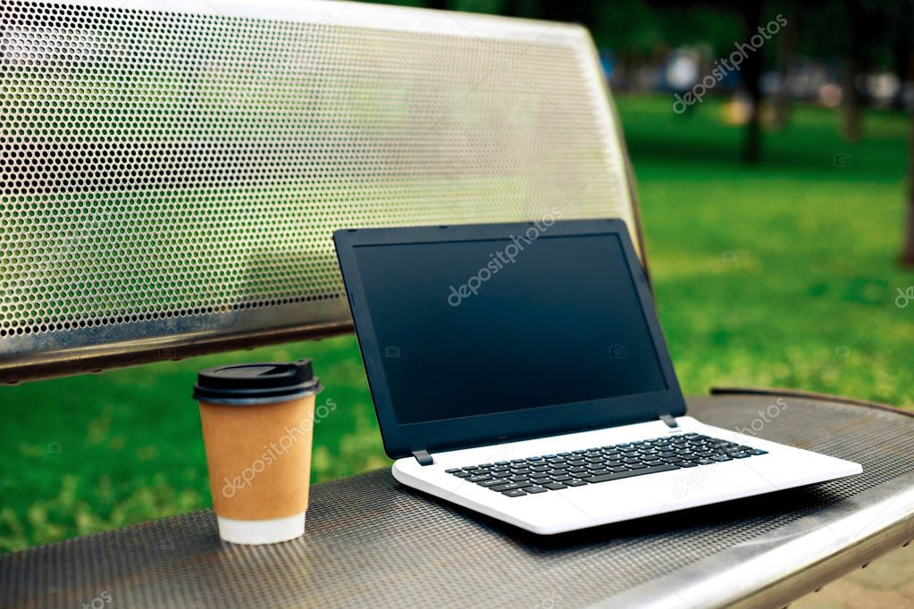Mockup image of laptop with blank black screen and coffee cup on metal bench in nature outdoor park