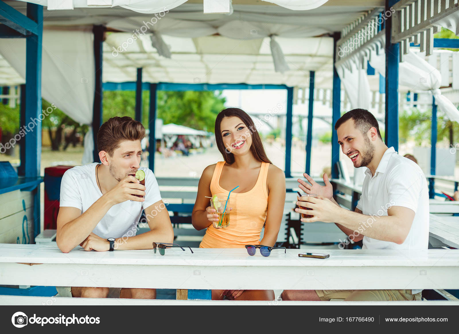 Friends toasting in summer vacation in a bar terrace on the beach