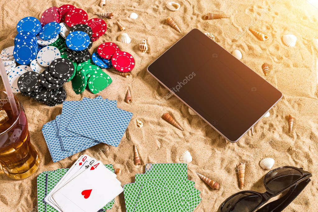 Gambling on vacation concept - white sand with seashells , colored poker chips and cards. Top view