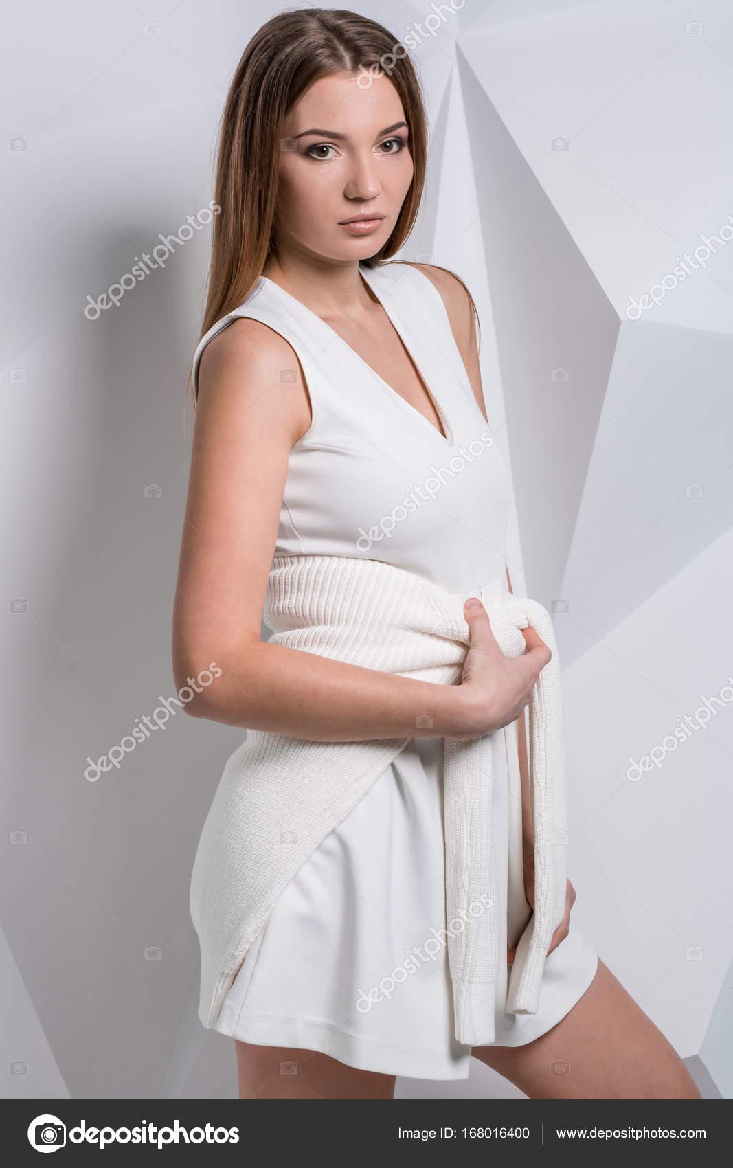 Schöne sexy junge Frau im weißen Kleid auf weißem Hintergrund ...