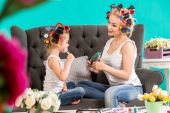 Portrait of cute little girl and her mom doing each other makeup