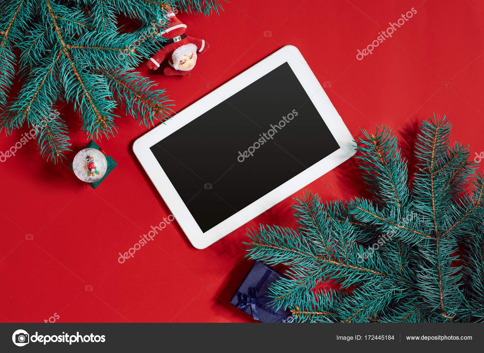 christmas decorations and white tablet with black screen on hot red background christmas and new year theme place for your text wishes logo mock up