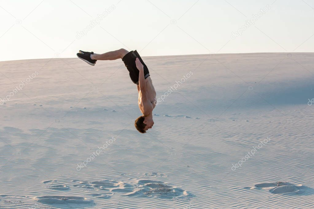 Man study parkour on their own. Acrobatics in the sand