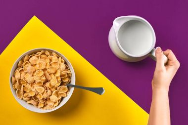 Food, healthy eating, people and diet concept - close up of woman eating muesli with milk for breakfast over purple and yellow background