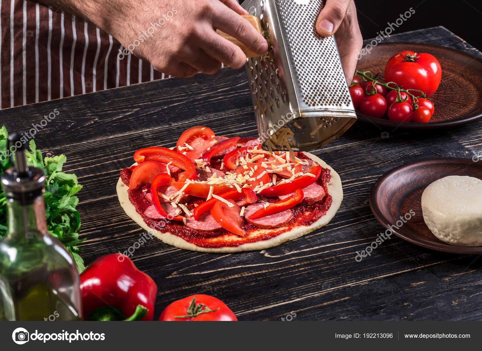 Kochen Sie in der Küche, die Zutaten auf der Pizza. Pizza-Konzept ...