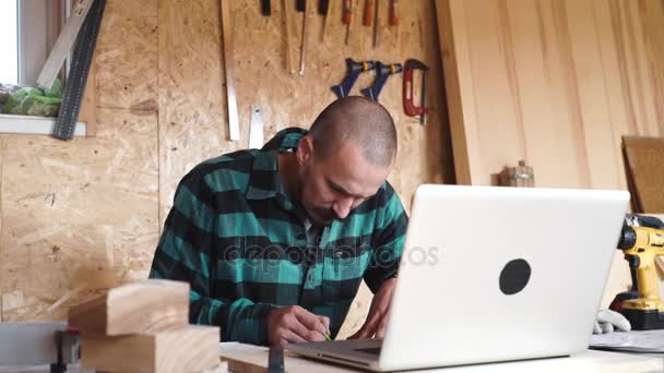 Bold with moustache young Carpenter Craftsman do drawing with laptop in his wooden workshop