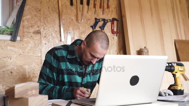 Tučně s knírem mladý truhlář řemeslník kreslení s notebookem v jeho dřevěná dílna