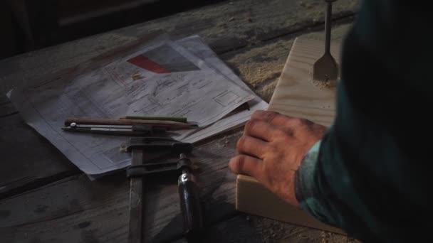 Tesaři rukou pomocí vrtáku na dřevěné prkno