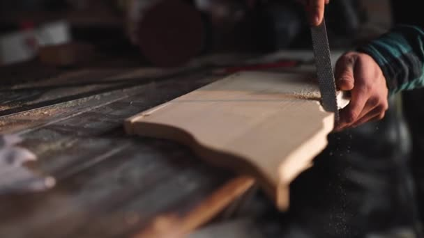 Close-up of a Carpenter working on a Wooden Window Frame with a File in his Workshop.