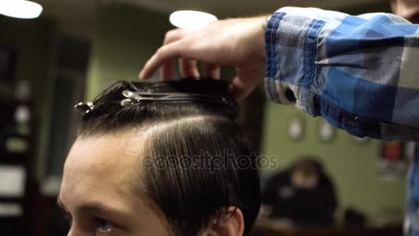 Long hair Barber cuts the hair of the client with scissors and comb in his barbershop