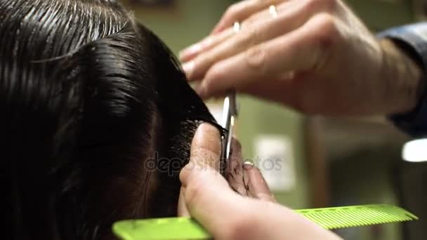 Hairstyling process. Close-up of a barber cutting hair of a young bearded man
