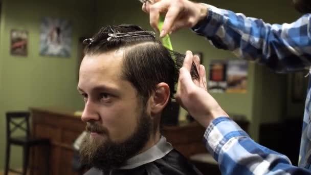Vnitřní záběr pracovního procesu v moderní holičství. Detail portrét atraktivní mladý muž dostává módní účes. Mužské kadeřník sloužící klienta, takže účes pomocí kovové nůžky a hřeben