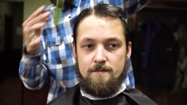 Barber making haircut of attractive bearded man in barbershop