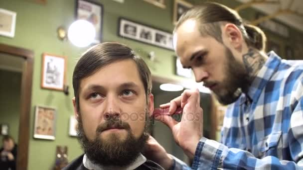 Barber making haircut of attractive bearded man in barbershop